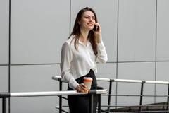 Donna felice di affari che sta e che parla sul telefono Immagine Stock