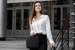 Donna felice di affari che sta sulla via e che tiene una borsa nera Immagini Stock Libere da Diritti