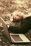 Donna felice di affari con il computer portatile che si trova sull'erba Fotografia Stock Libera da Diritti