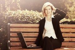 Donna felice di affari con il computer portatile nel parco della città Fotografia Stock Libera da Diritti