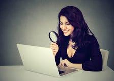Donna felice di affari con la lente d'ingrandimento che esamina computer portatile che si siede allo scrittorio Fotografia Stock