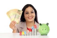 Donna felice di affari con la pila di monete e di tenuta delle note della rupia Fotografie Stock