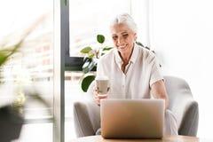 Donna felice di affari maturi che lavora al computer portatile fotografia stock