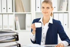 Donna felice di affari o ragioniere femminile che ha determinati minuti per caffè e piacere al posto di lavoro fotografia stock libera da diritti
