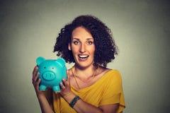 Donna felice di affari, porcellino salvadanaio della tenuta degli impiegati della banca Immagine Stock