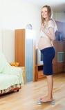Donna felice di gravidanza sulla bilancia pesa-persone Fotografie Stock Libere da Diritti