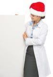 Donna felice di medico in cappello di Santa che considera tabellone per le affissioni in bianco Fotografia Stock