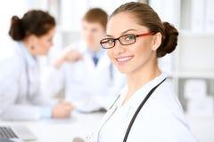 Donna felice di medico con il personale medico all'ospedale che si siede alla tavola Vetri rossi della struttura immagini stock libere da diritti