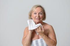 Donna felice di medio evo che asciuga il suo collo con l'asciugamano Fotografie Stock
