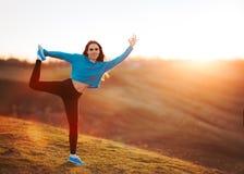 Donna felice di misura che allunga in natura al tramonto Fotografia Stock