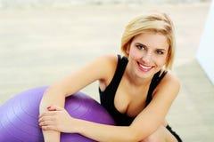 Donna felice di misura che si siede sul pavimento con fitball Immagini Stock Libere da Diritti