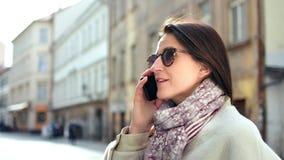 Donna felice di modo che parla facendo uso dello smartphone che cammina sulla via della città che ha buon tempo all'aperto stock footage