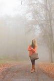 Donna felice di modo con la borsa nel parco di autunno Fotografia Stock