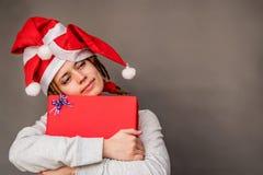 Donna felice di Natale che abbraccia un presente piacevole di rosso Fotografia Stock Libera da Diritti