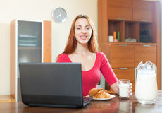 Donna felice di Pssitive nel rosso facendo uso del computer portatile durante la prima colazione a hom Fotografia Stock Libera da Diritti