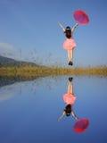 Donna felice di riflessione dell'acqua che salta con il cielo blu Fotografie Stock Libere da Diritti