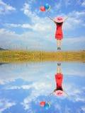 Donna felice di riflessione dell'acqua che salta con il cielo blu Fotografia Stock