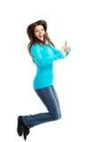 Donna felice di vista laterale che salta con i pollici su Fotografia Stock