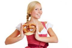 Donna felice in dirndl con la ciambellina salata Immagini Stock