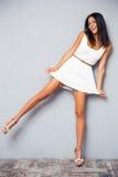 Donna felice divertente che sta su una gamba fotografia stock