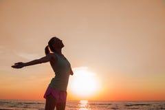 Donna felice dopo l'allenamento che sta nel tramonto Immagini Stock Libere da Diritti