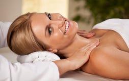 Donna felice durante il massaggio del collo Immagini Stock