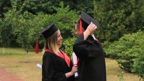 Donna felice ed uomo in vestiti accademici che abbracciano dopo la graduation archivi video