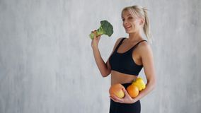 Donna felice esile che tiene frutta e le verdure fresche archivi video