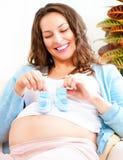 Donna felice incinta che tiene le scarpe di bambino blu Fotografie Stock