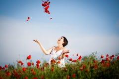 Donna felice incinta in un campo di fioritura del papavero immagine stock libera da diritti