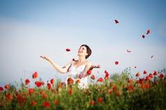 Donna felice incinta in un campo di fioritura del papavero Immagine Stock