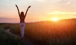 Donna felice libera che alza armi al tramonto nel campo immagini stock libere da diritti