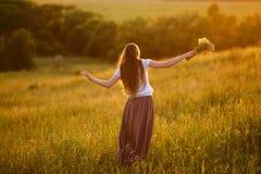 Donna felice nel campo con un mazzo dei fiori Fotografia Stock