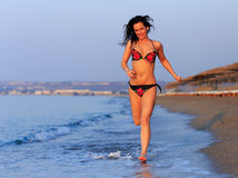 Donna felice nel funzionamento del costume da bagno sulla spiaggia Immagini Stock Libere da Diritti