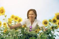 Donna felice nel giacimento del girasole che sorride con la felicità Immagini Stock