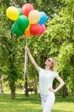 Donna felice nel parco con i palloni Fotografia Stock