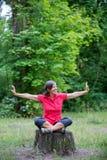 Donna felice nel suo 50s che si siede su un ceppo di albero Fotografie Stock