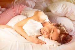 Donna felice in pigiama che dorme a letto Immagini Stock
