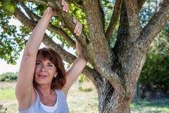 Donna felice 50s sotto l'albero per la metafora di serenità Fotografie Stock