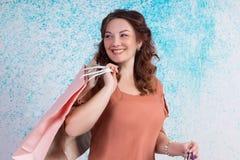 Donna felice in sacchi di carta arancio di acquisto della tenuta della blusa Fotografia Stock Libera da Diritti