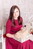 Donna felice sul giftbox della tenuta del sofà immagini stock