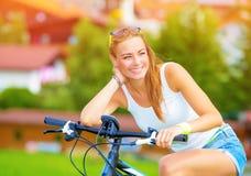 Donna felice sulla bicicletta Fotografie Stock