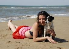 Donna felice sulla spiaggia con il suo cane Fotografia Stock Libera da Diritti