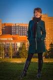 Donna felice in un cappotto scuro che sta all'aperto autunno al tramonto fotografia stock libera da diritti