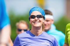 Donna felice in un gruppo di corridori nella maratona 20 di Stoccolma di ASICS Immagini Stock Libere da Diritti