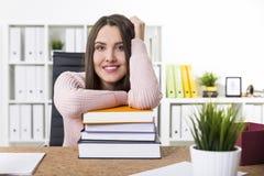 Donna felice in un maglione rosa e una pila di libri Immagini Stock Libere da Diritti