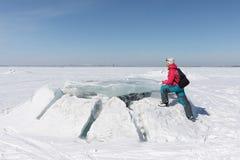 Donna felice in un rivestimento rosso che fa un passo su una banchisa sull'congelata Immagine Stock
