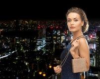 Donna felice in vestito da sera con la piccola borsa Immagine Stock
