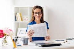 Donna felice in vetri che legge giornale all'ufficio Immagini Stock