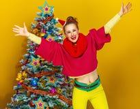 Donna felice vicino all'albero di Natale sull'esultanza gialla del fondo fotografie stock libere da diritti
